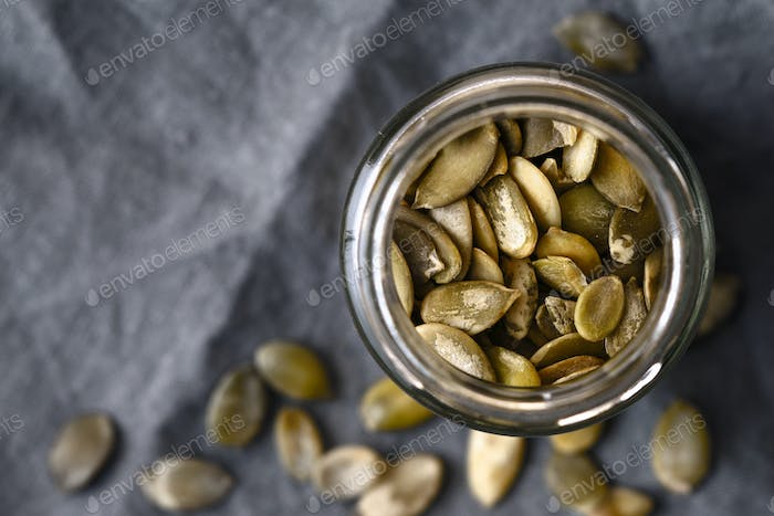 Pumpkin seeds in the glass jar cloth-up