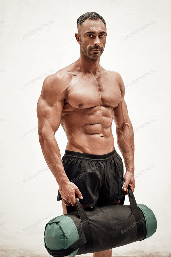 Handsome athlete wearing sportswear posing with sand bag and looking at the camera in a dark studio