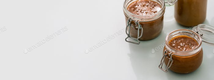 Salted caramel in glass jars, banner