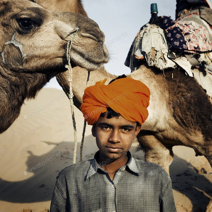 Young Indian Boy with Camels Desert Concept