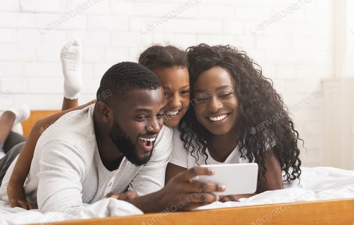 Smiling african father taking selfie with his wife and daughter
