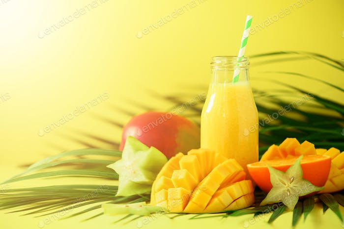 Delicious juicy smoothie with orange fruit and mango on yellow background. Copy space. Pop art