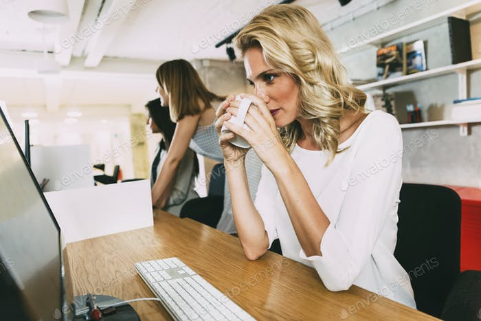 Beautiful businesswoman drinking tea to stay alert