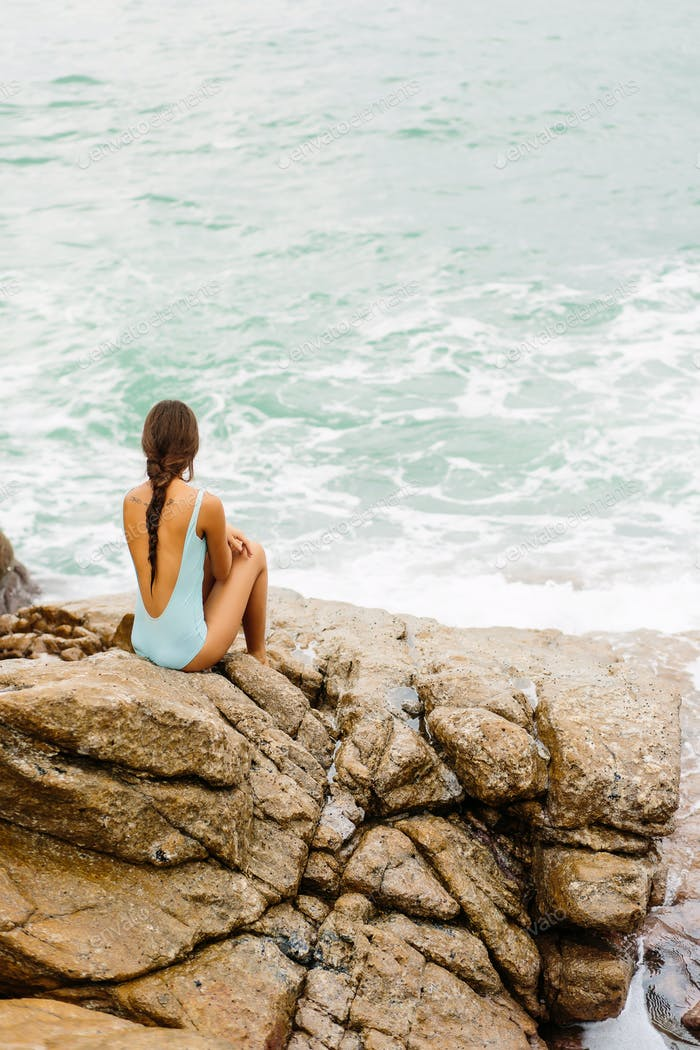 Beautiful girl in blue swimsuit sit on big stone.