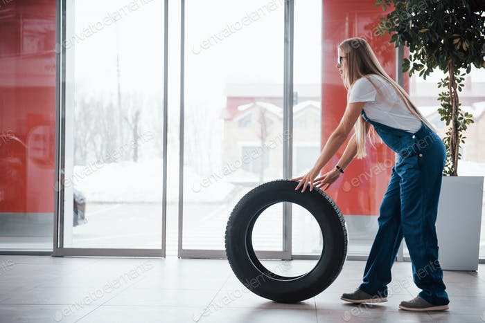 Doors is opening. Woman walks with brand new wheel to the car. Conception of repair