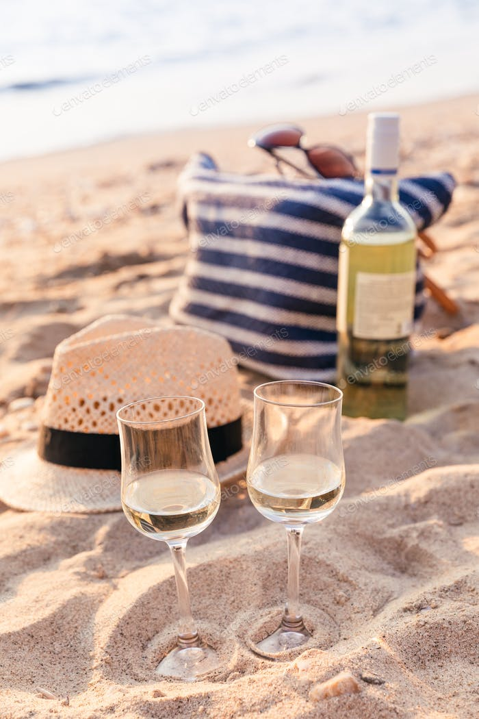 Glasses of the white wine on the sunset beach, picnic theme
