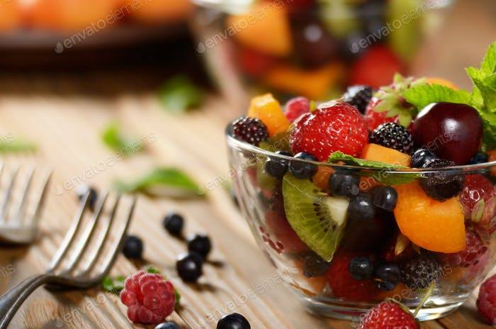 Assorted fruits in glass bowl on kitchen wooden table with fork