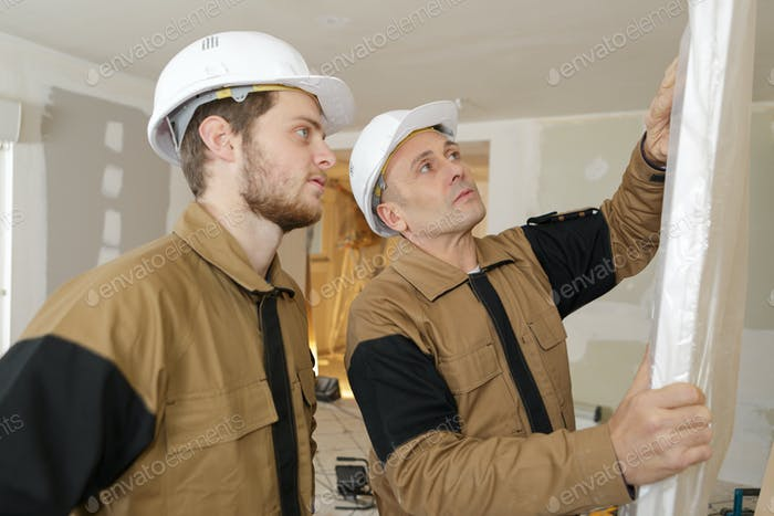 constructor and apprentice verifies correct installation on garage door panel