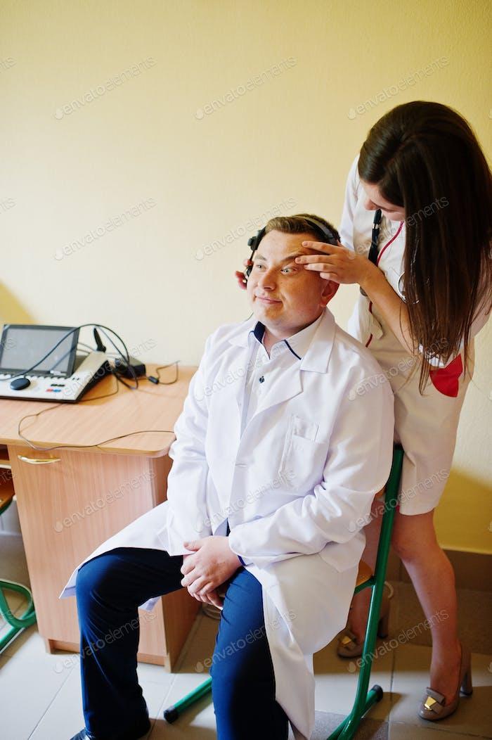 Attraktive Ärztin im weißen Kittel, die die Gesundheit ihrer Patientin untersucht.