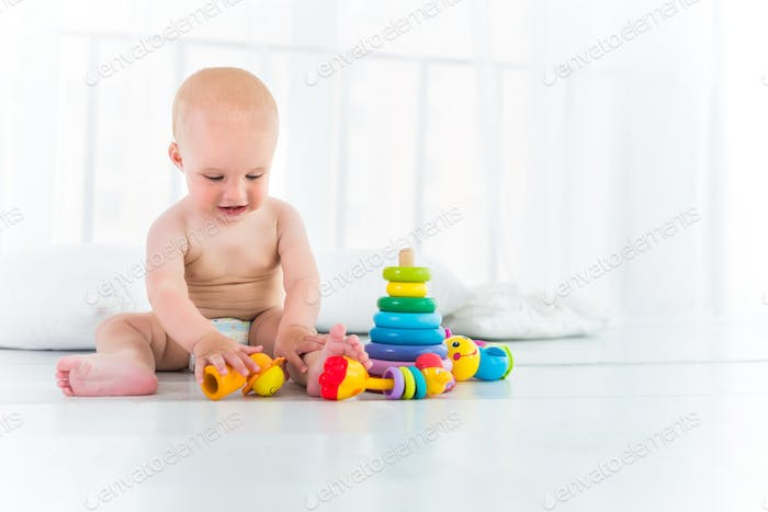 Charming cheerful kid in a diaper laughs