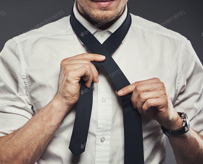 junge Geschäftsmann binden seine Krawatte für die Arbeitstag