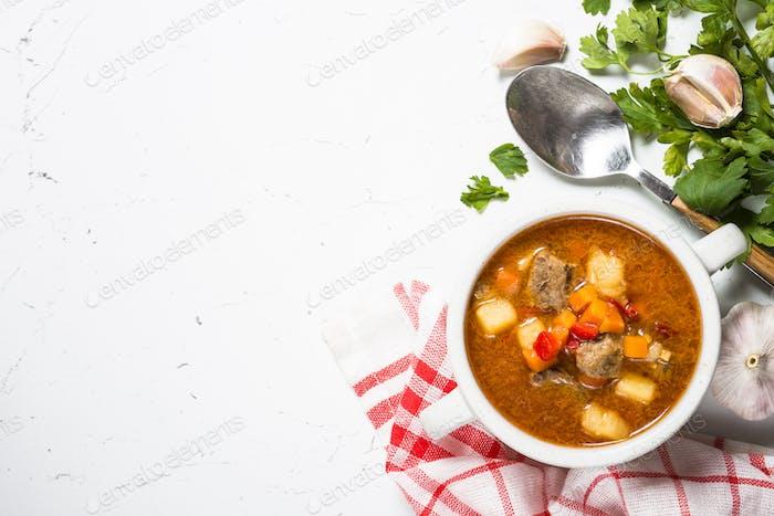 Goulash soup on white stone table top view