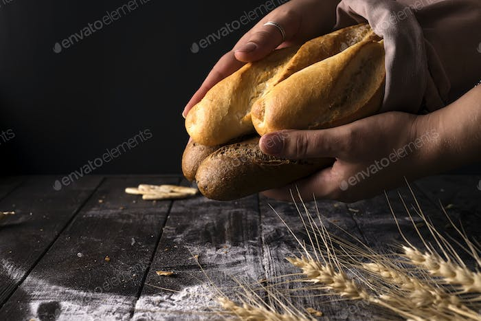 Baker woman holding rustic organic loaf of bread in hands - rural baker