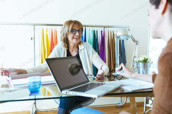 Two business women talking about work and exchanging ideas in the office.