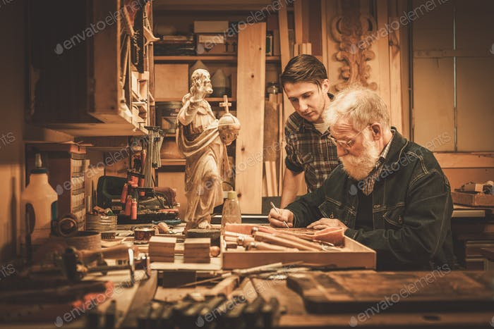 Senior restorer and his apprentice working with antique decor element in his workshop