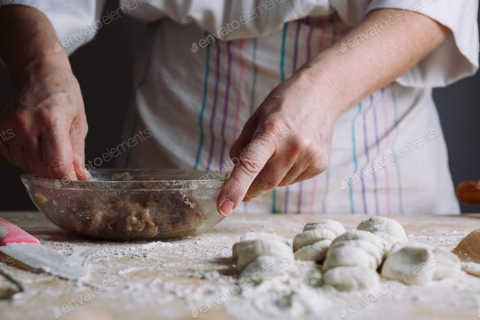 Two hands making meat dumplings.
