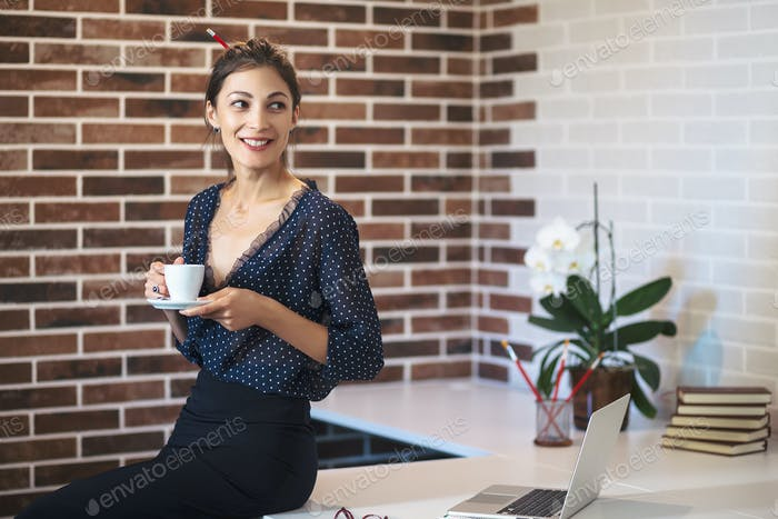 Woman holding a cup of coffee in hands smiling happy