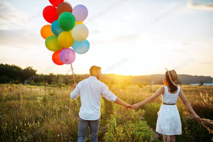 Couple holds balloons and kissing in wheat field