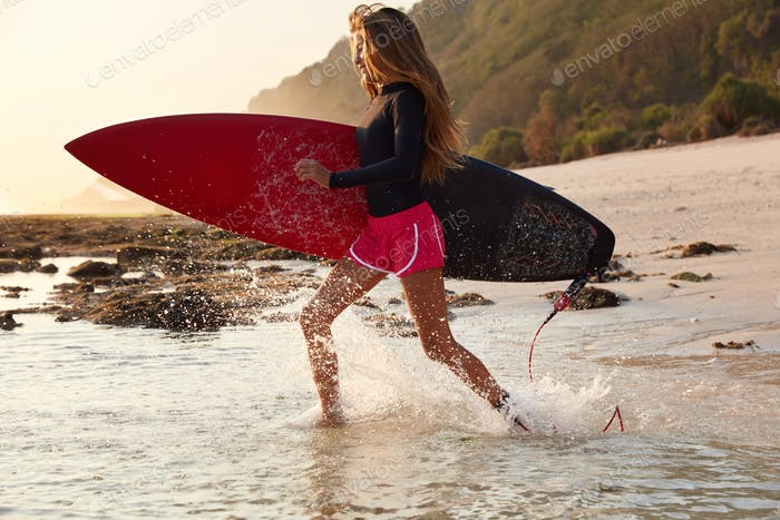 Horizontal shot of active woman likes surfing, cant imagine life without extreme water sport, being