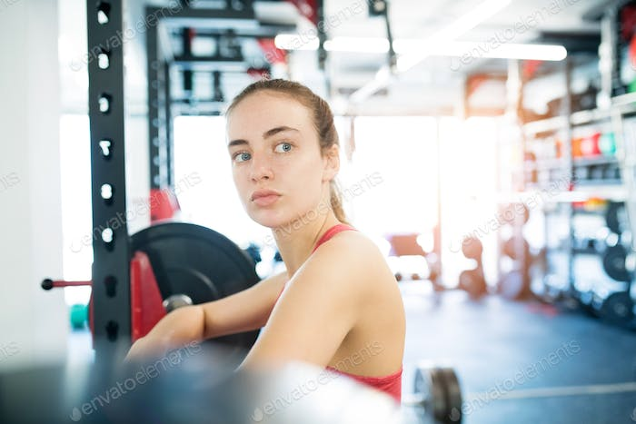 Young woman in gym standing at the heavy barbell