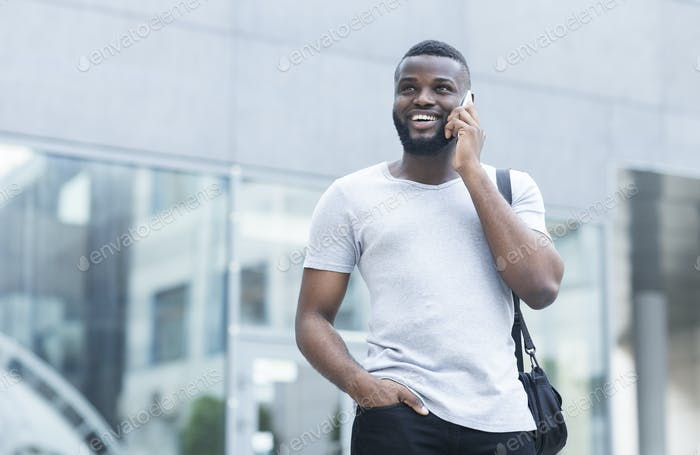 Young african man talking on phone with friend and smiling