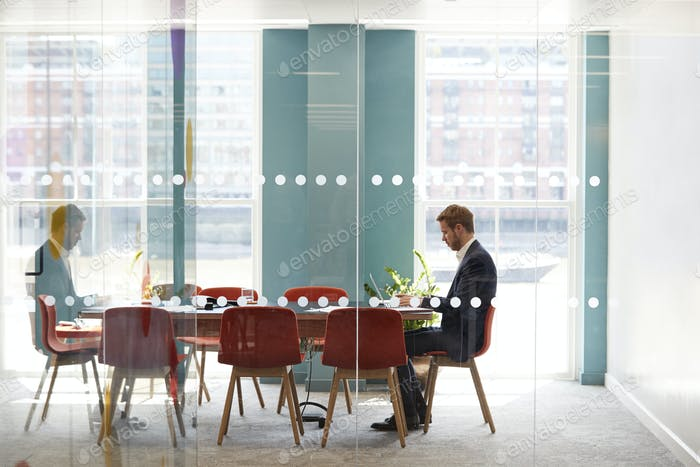 Young businessman working alone in an office meeting room