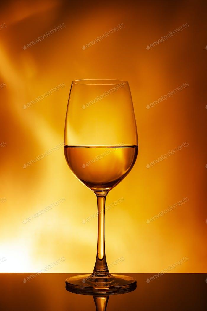 Glass of white wine on an orange background