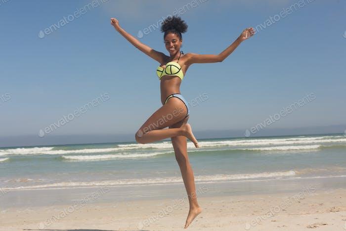 Happy young woman in green bikini jumping on the beach