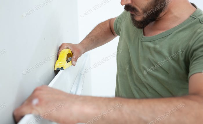 Worker building plasterboard wall.