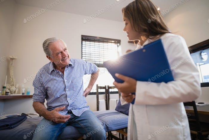 Senior male patient showing back ache to female therapist with file