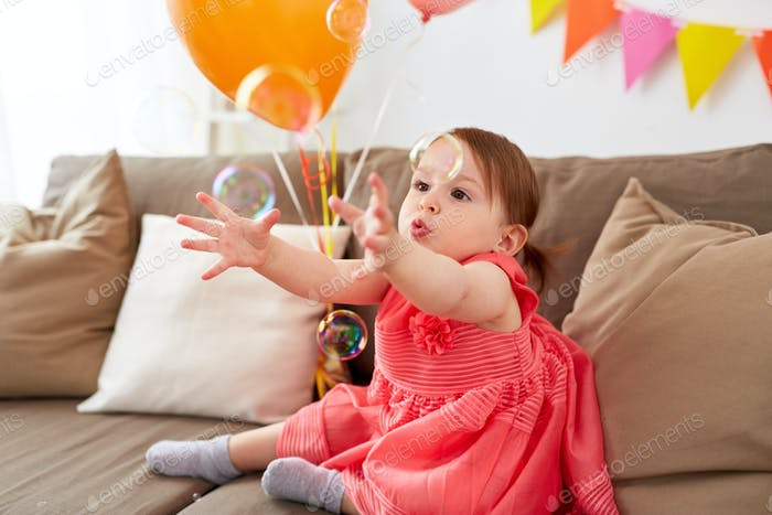 baby girl with soap bubbles on birthday party