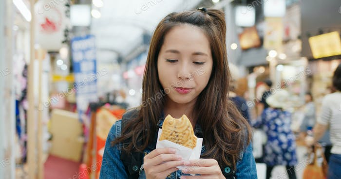 Woman travel in Japan and enjoy the local food Taiyaki in the Tokyo city