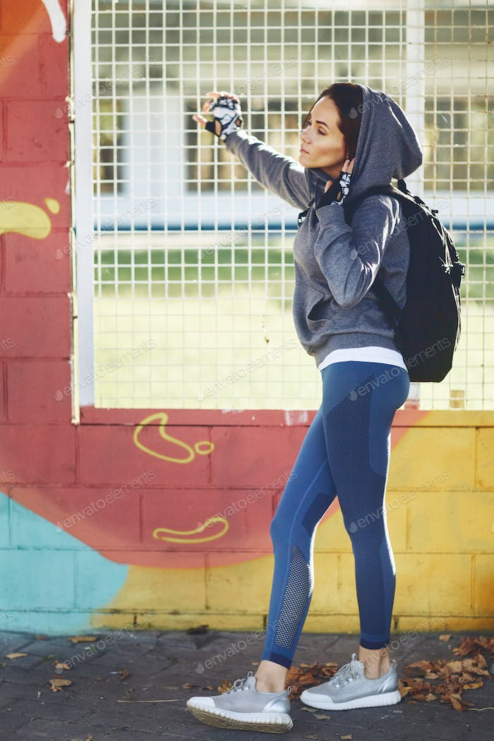 A brunette girl in a hoodie stands against a colored wall in thought and dreams.