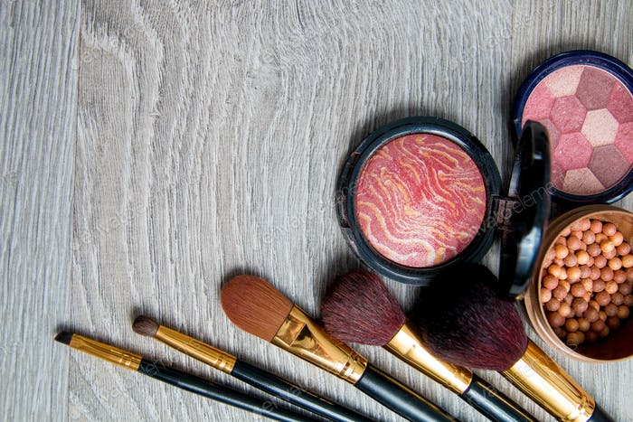 Set of decorative cosmetics and brushes on grey wooden background. Various browns makeup products.