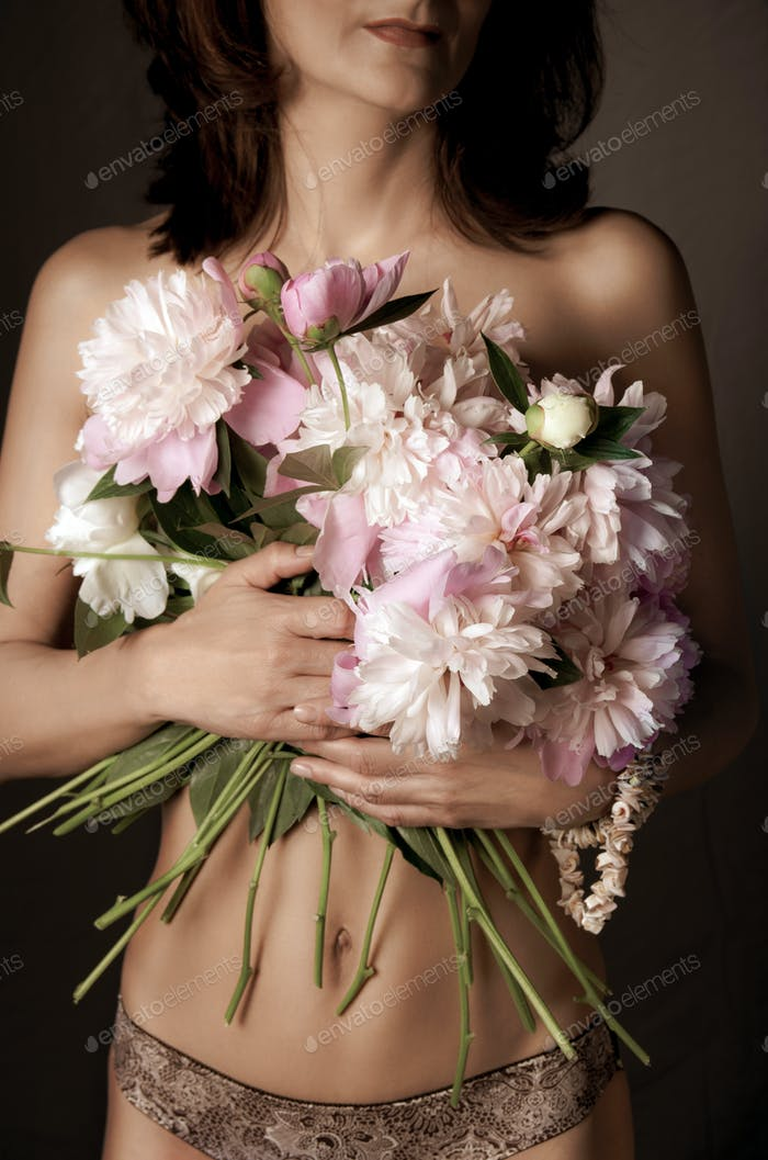 Half-naked middle age brunette caucasian model with peonies studio shot