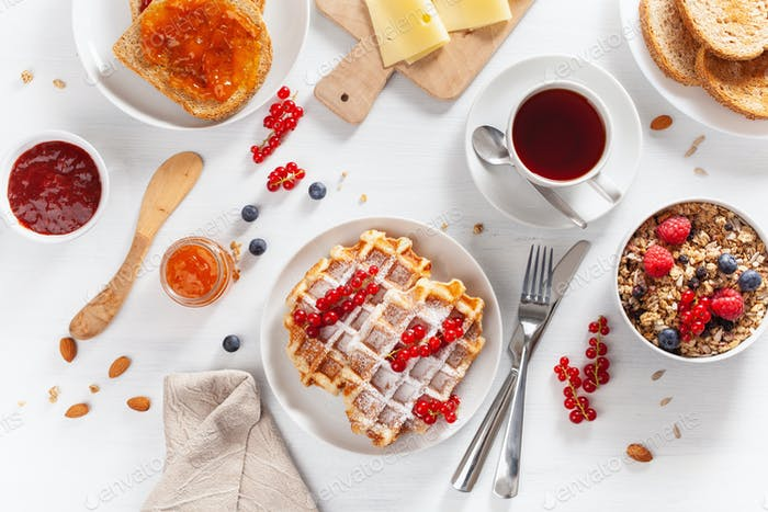 breakfast with granola berry nuts, waffle, toast,  jam and tea.