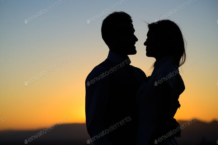 silhouette of bride and groom on Sunset background