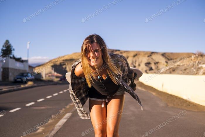 lindo modelo hermoso rubio pelo largo sonrisa a usted en la cámara caminando en un largo camino