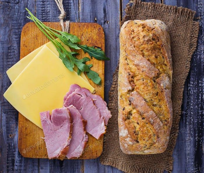Ingredients for sandwich: cheese, arugula, ham.
