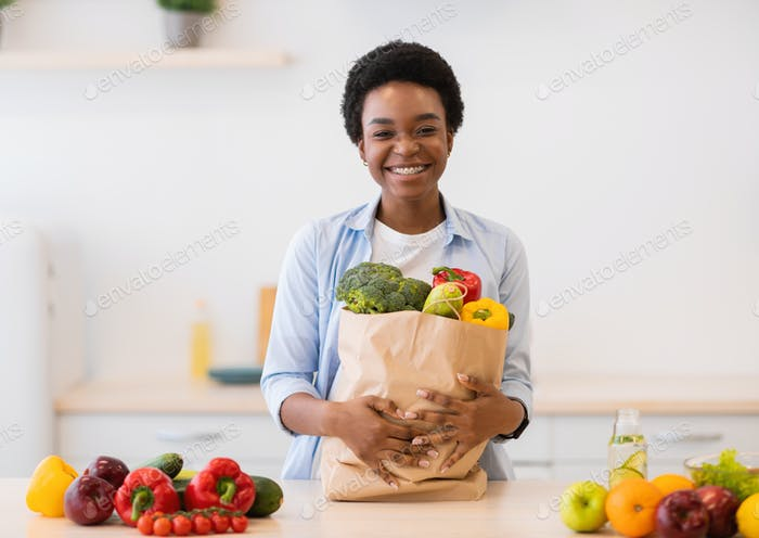 Woman Holding Grocery Shopping Bag Full Of Vegetables In Kitchen