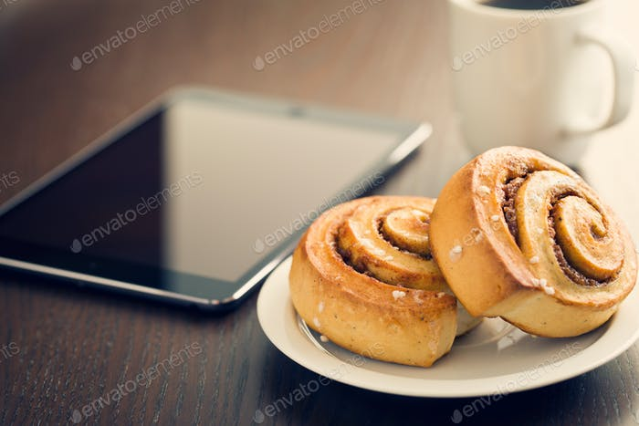 cinnamon rolls, cup of coffee and computer tablet