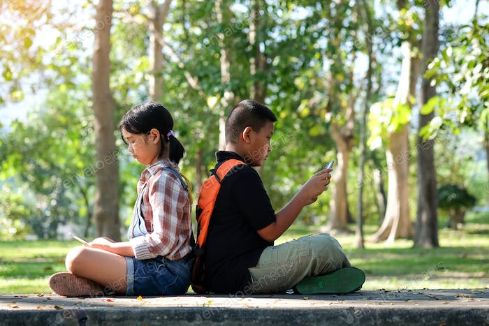 Asian children are playing a tablet in the park.