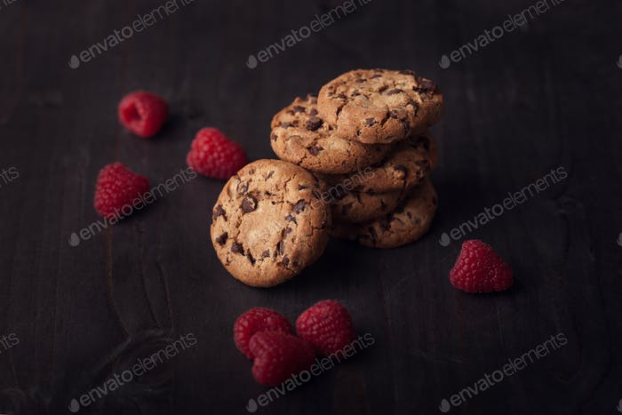 Chocolate chip cookies on dark old wooden table with red raspberry