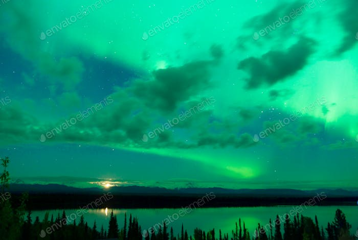 The Aurora Borealis emerges through clouds remote Alaska