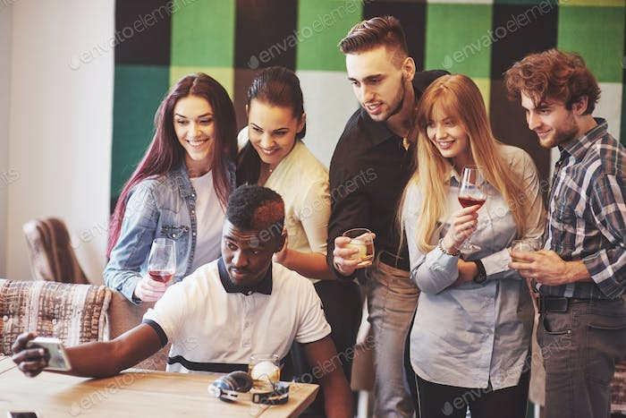Friends having fun at restaurant. Three boys and three girls making selfie and laughing. On