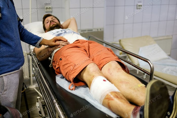 Young man lying in a hospital bed in the building of ambulance after a car accident
