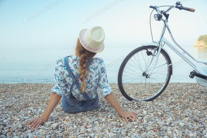 Woman with bicycle on the beach - view from the back