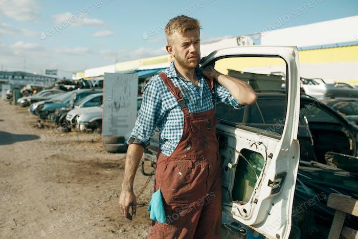 Männlicher Reparaturmann hält Tür auf dem Auto Schrottplatz