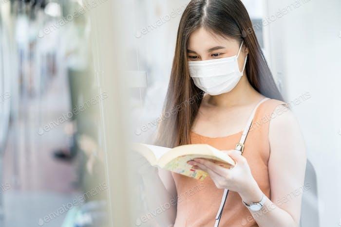 Mujer joven asiática pasajera con máscara quirúrgica y la lectura del libro en el tren del metro