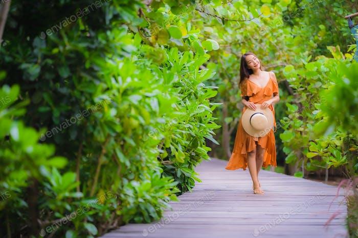 Portrait beautiful young asian woman walk on path walk in the ga